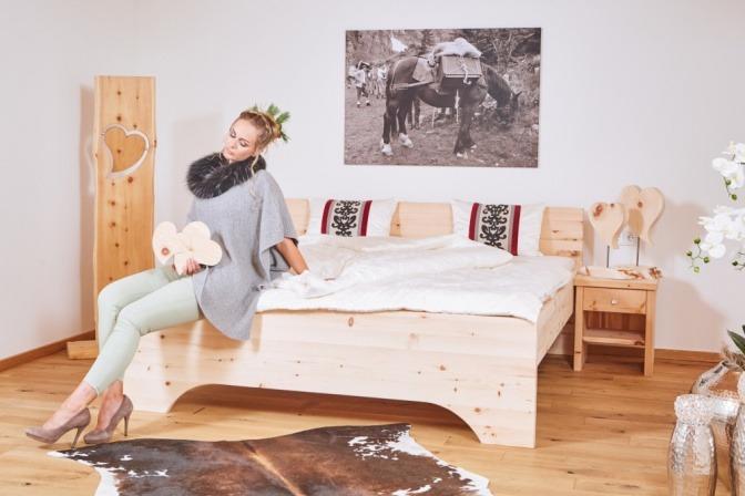 Eine Frau sitzt neben einem Bett, das keine Störquelle im Schlafzimmer ist