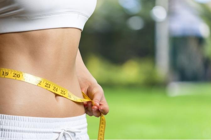 Eine Frau misst ihren schlanken Körper