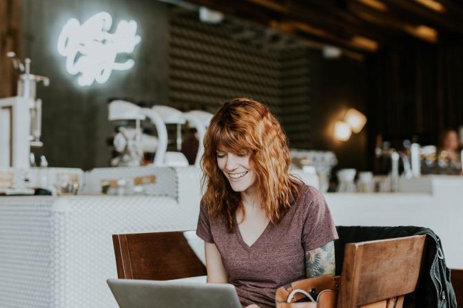 Eine Frau sitzt lächelnd in einem Sessel während sie auf einen Laptopbildschirm schaut.
