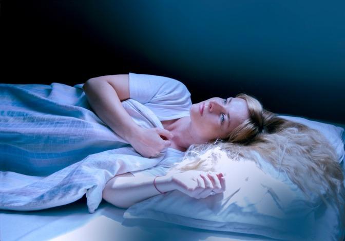 Eine Frau liegt nachts wach und schaut durch das Dachfenster zum Mondlicht auf.