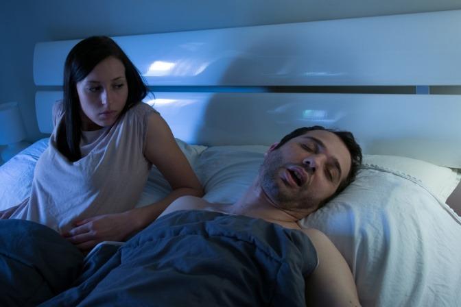 Eine Frau hat aufgrund von Vollmond Schlafprobleme und blickt neidisch auf Ihren selig schlafenden Partner im Bett.