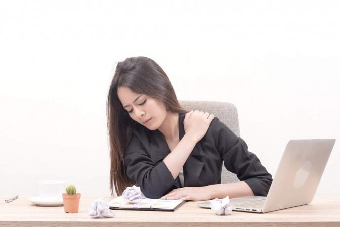 Frau vor Computer am Schreibtisch greift sich an die Schulter.