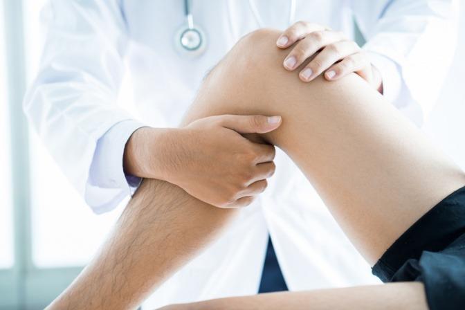 Ein Mann sitzt beim Arzt und lässt das Gelenk vom Knie untersuchen