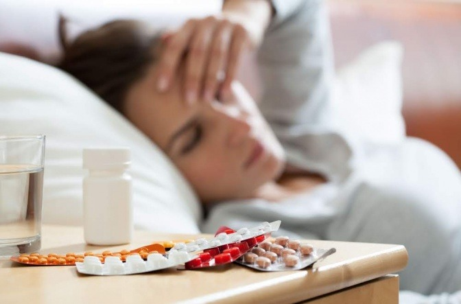 Frau mit Schmerzen und Tabletten am Nachttisch