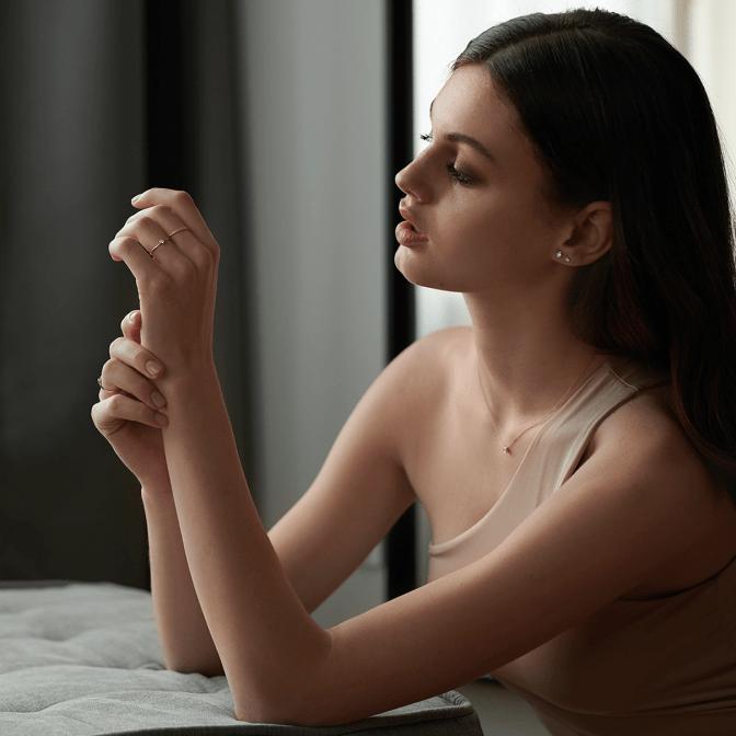 Eine Frau trägt minimalistischen Schmuck