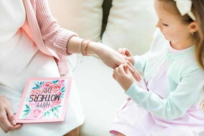 Ein Mädchens streift seiner Mutter Armbänder über