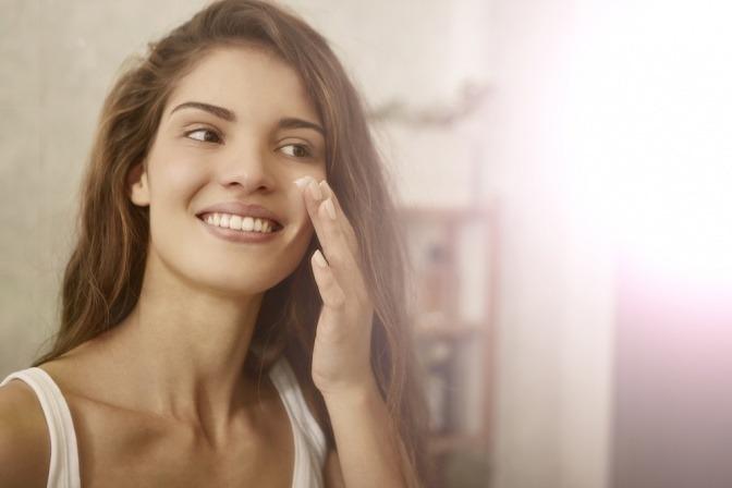 Frau cremt ihr Gesicht ein für schöne Haut
