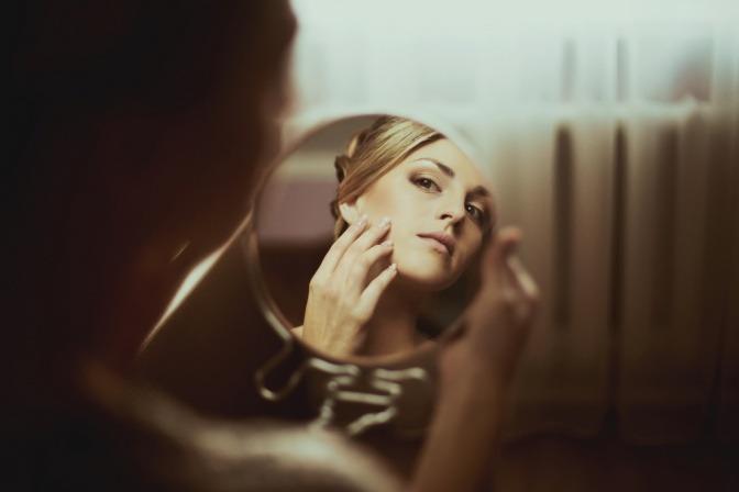 Frau sieht in den Spiegel