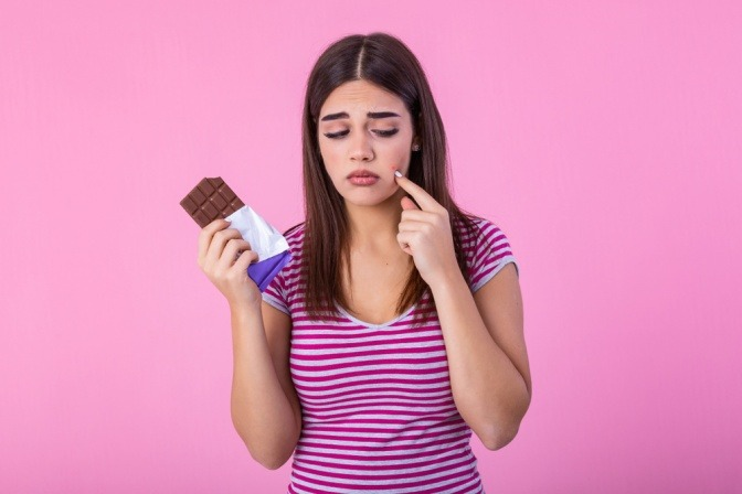 Frau mit Schokolade und Akne