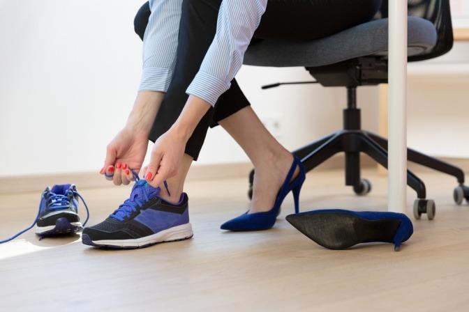 Frau wechselt von High-Heels auf Sneaker.