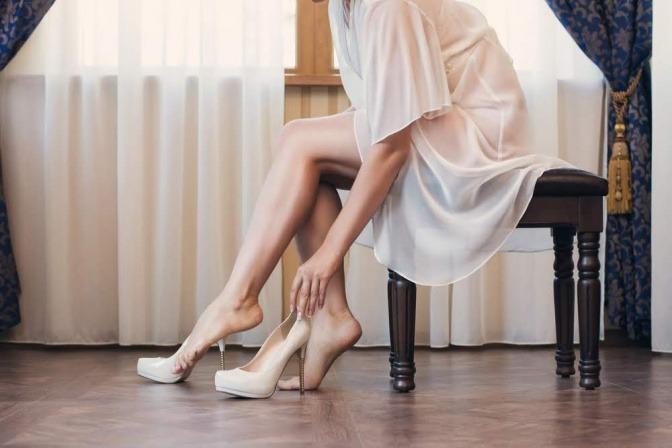 Eine Frau sitzt an ihrem Schreibtisch und zieht sich gerade die Schuhe aus, dabei fasst sie sich an die linke Ferse.