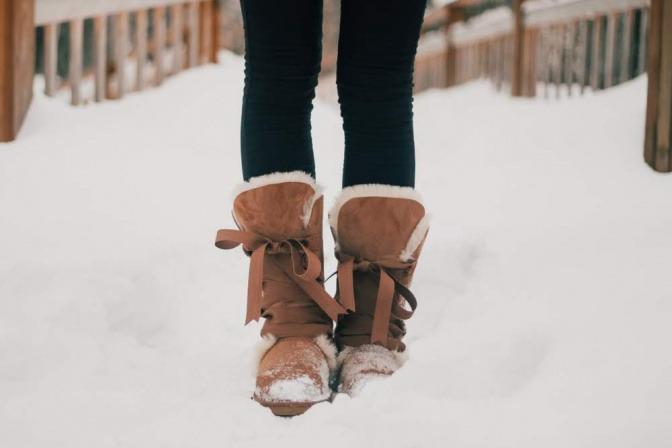 Frau mit Lederstiefel im Schnee.
