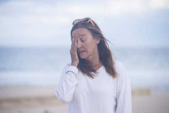 Eine Frau macht einen Spaziergang am Strand. Sie wirkt nachdenklich und scheint gerade eine Erkenntnis zu haben, vielleicht bezüglich ihrer Schuldgefühle.