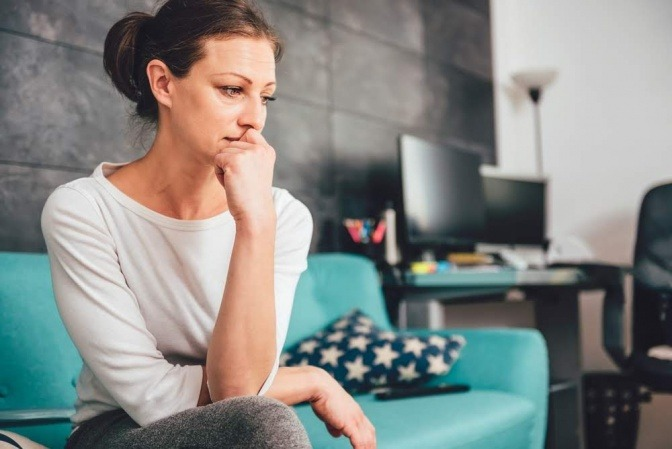 Eine Frau mit einem traurigen Gesicht sitzt auf einem Sofa. Vielleicht überlegt sie sich, wie sie ihre Schuldgefühle loswerden kann.