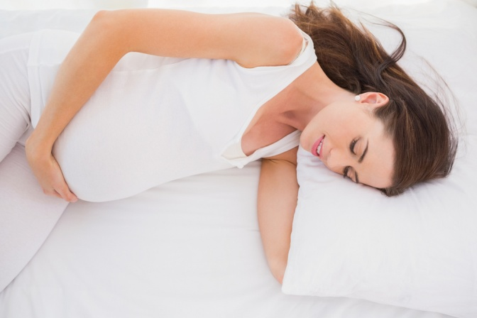 Eine schwangere Frau liegt auf der Seite und hat ein Kissen unter dem Arm