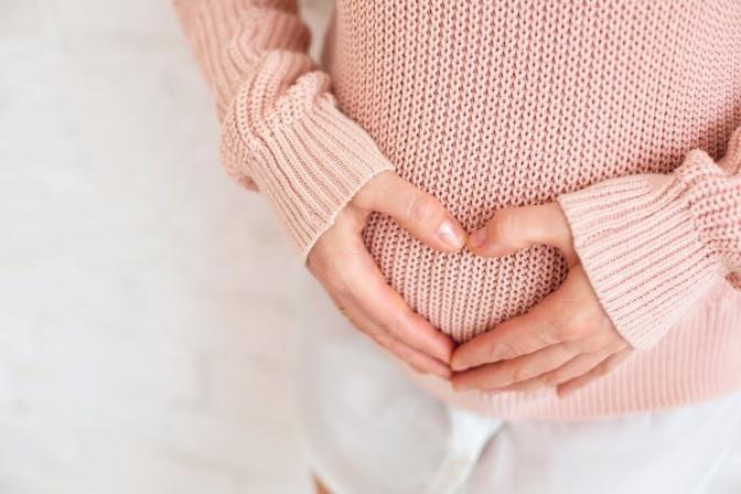 Bauch einer Schwangeren die ein Herz mit ihren Händen darauf formt.