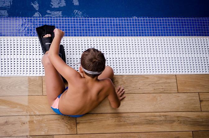 Bub mit Taucherflossen vor Schwimmbecken.