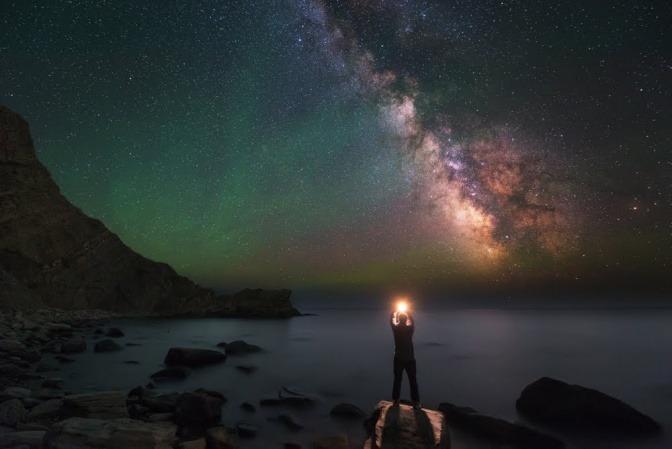 Ein Mann steht im Dunkeln auf einem Stein in einer Bucht und hält eine stark leuchtende Kugel in den Händen, die er in den Himmel streckt.