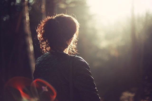 Eine Frau blickt in seelischer Balance in die Sonne