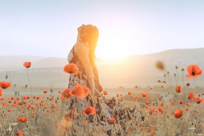 Eine Frau steht mit Sehnsucht nach Selbstfindung in einem Feld