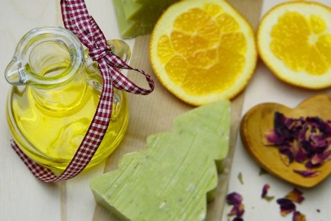 Verschiedene Zutaten zum Seife selbst machen wie Öle und Kräuter liegen auf einer Oberfläche nebeneinander.