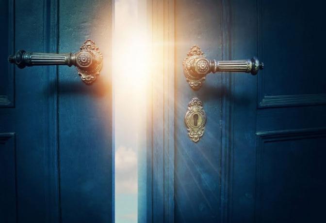 Eine hölzerne, zweiflügelige Tür ist einen Spalt breit geöffnet. Man erkennt dahinter gleißendes Sonnenlicht.