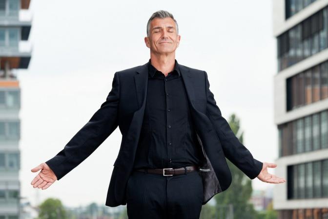Ein Mann steht selbstbewusst vor Häusern