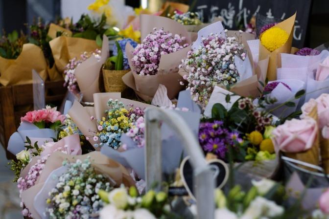 Diverse Blumensträuße mit Wiesenblumen vor dem Eingang eines Ladens.