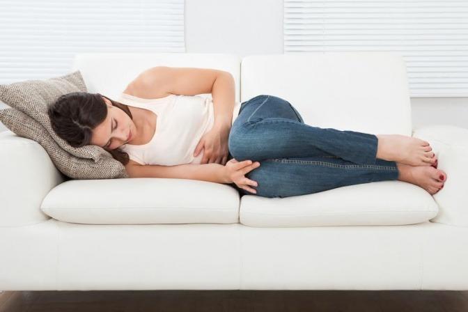 Frau mit Bauchschmerzen auf der Bank