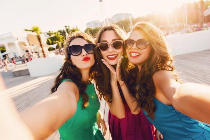 Drei Freundinnen stehen bei Sonnenuntergang an einem Pier und machen ein Selfie.