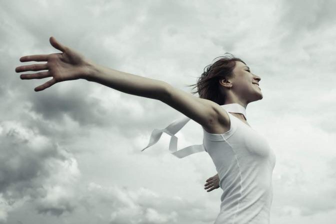 Eine Frau in einem luftigen weissen Kleid spreizt die Arme und blickt motiviert nach vorne, während sich über ihr dunkle Gewitterwolken auftun.