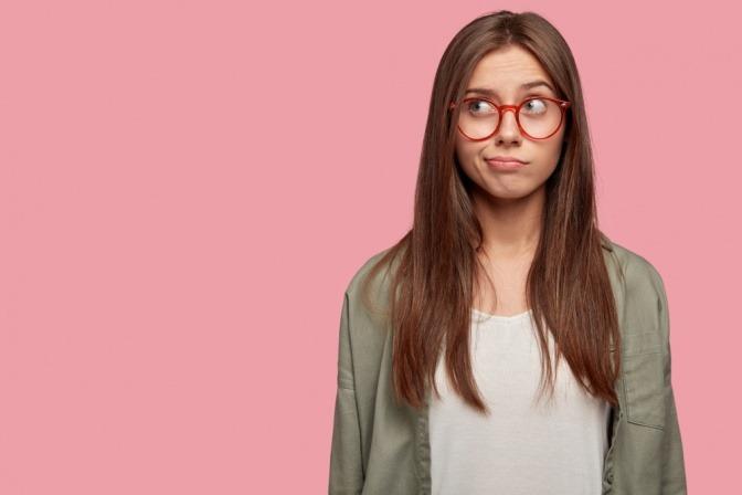 Junge Frau mit Brille wirkt unsicher und blickt fragend nach oben.