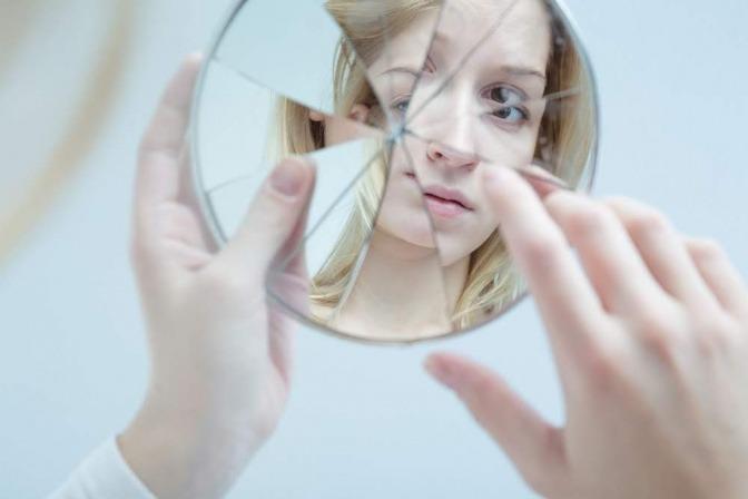 Eine Frau blickt in einen Handspiegel, dessen Oberfläche zerbrochen ist.