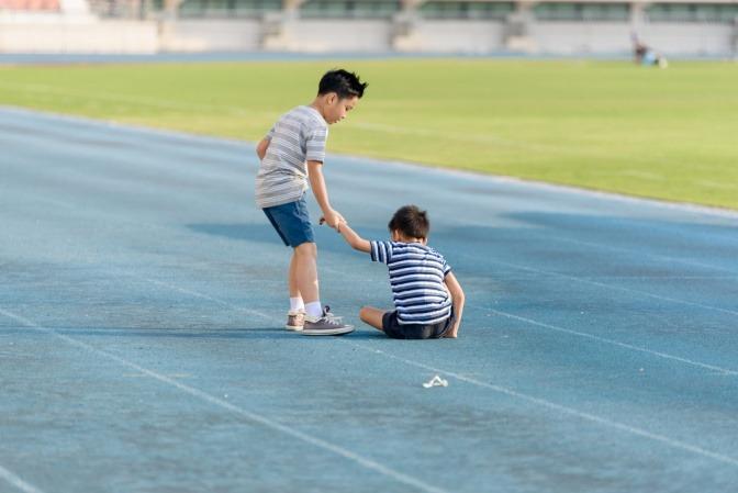 Ein kleiner Junge hilft einem anderen Kind wieder aufzustehen, nachdem es bei einem Rennen auf einer Tartanbahn hingefallen ist.
