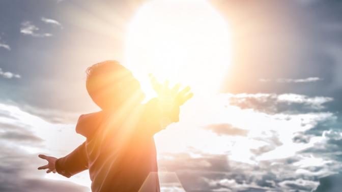 Eine Frau steht selbstzentriert vor Sonnenschein