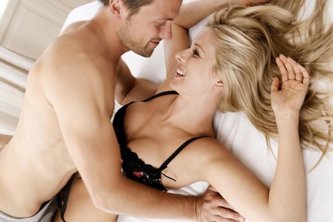 Ein Paar ist im Bett und sieht glücklich aus