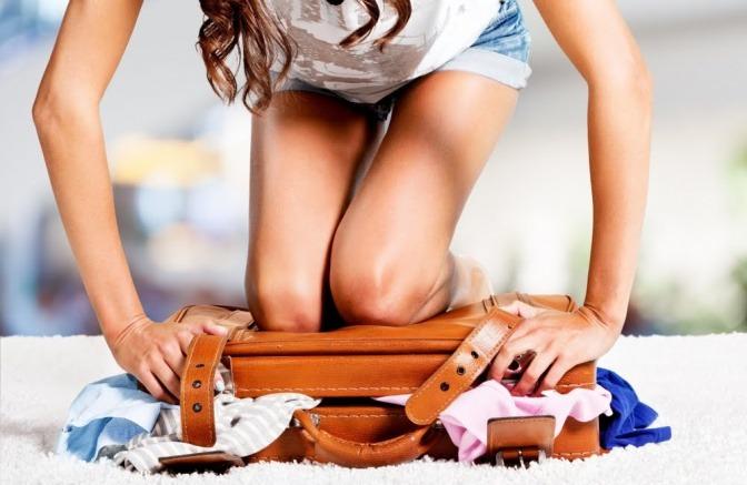 Eine Frau sitzt auf ihrem überfüllten Reisekoffer