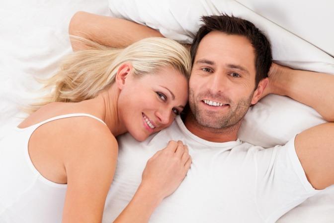 Eine Frau und ein Mann im mittleren Alter liegen im Bett. Sie hat ihren Kopf auf seinen Schultern gelegt. Beide lächeln in die Kamera.
