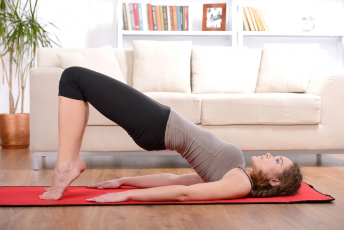 Eine brünette Frau liegt auf einer roten Sportmatte und hebt ihr Becken. Ihre Arme sind dabei am Boden und im Hintergrund ist eine weiße Couch zu sehen.