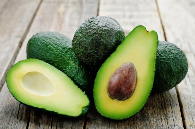 Auf dem Foto sind mehrere Avocados abgebildet. Sie liegen auf einem hölzernen Untergrund. Die vorderste Avocado ist in zwei Teile aufgeschnitten.