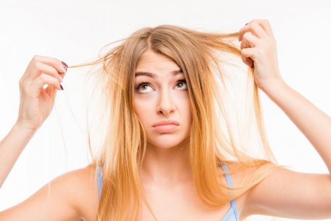 Eine Frau mit blonden verfilzten Haaren hält sich beide Hände ins Haar