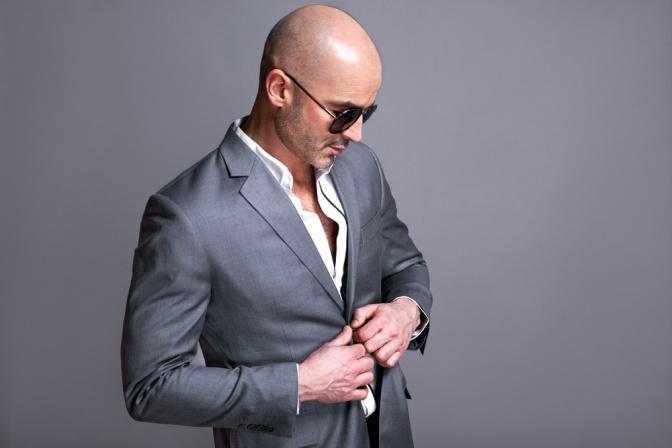 Ein Mann mit Glatze und Sonnenbrille trägt einen Anzug