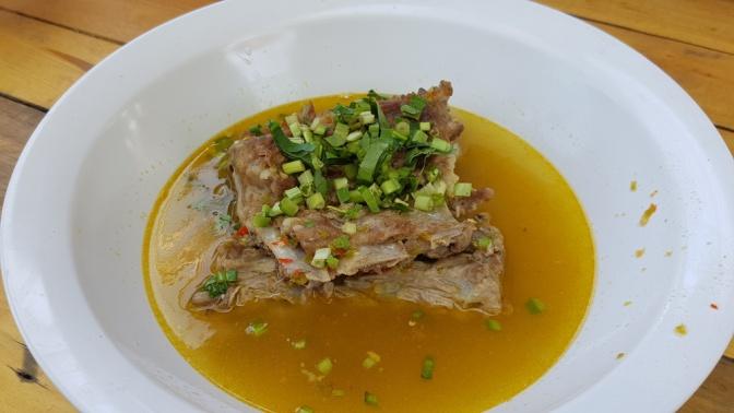 Ein Suppenteller mit Fleisch und Suppe ist abgebildet. Das Teller ist weiß. Das Fleisch ist mit Schnittlauch garniert.