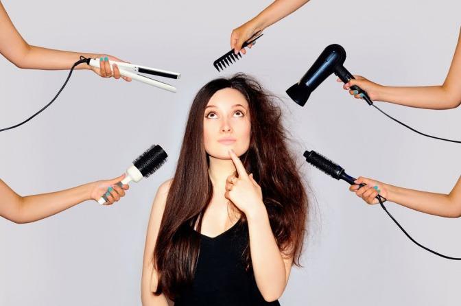 Eine Frau mit langen braunen Haaren umgeben von verschiedensten Stylingutensilien