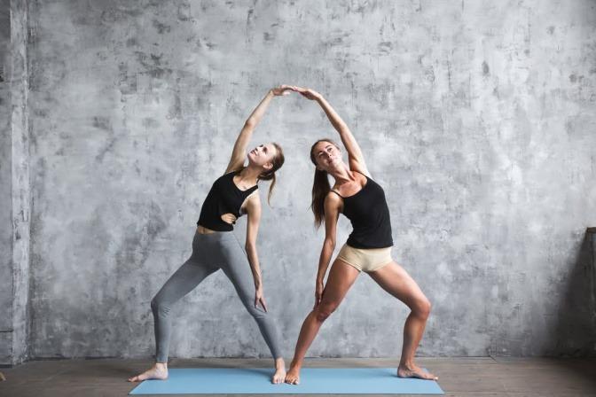 Zwei Frauen machen Partner-Yoga