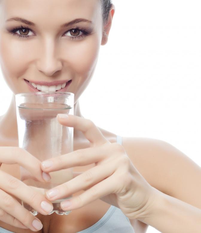 Eine braunhaarige Frau lächelt in die Kamera. Sie hält ein Glas Wasser an ihre Lippen. Ihre Augen sind braun. Der Hintergrund ist weiß.