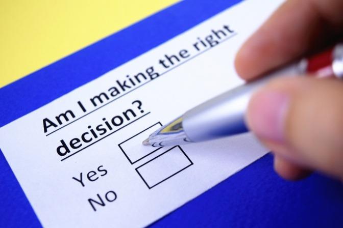 Ein Kugelschreiber liegt neben zwei leeren Kästchen mit der Aufschrift yes und no