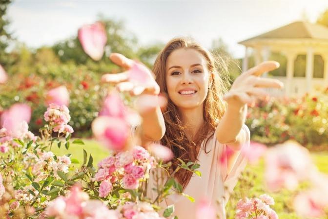Eine junge Frau steht mitten in einem prachtvoll blühenden Blumenfeld. Sie wirft ein paar Blüten nach oben und wirkt zufrieden und selbstbewusst.
