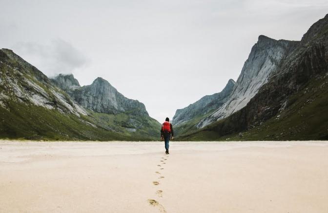 Eine einsame Backpackerin geht an einem Strand entlang.