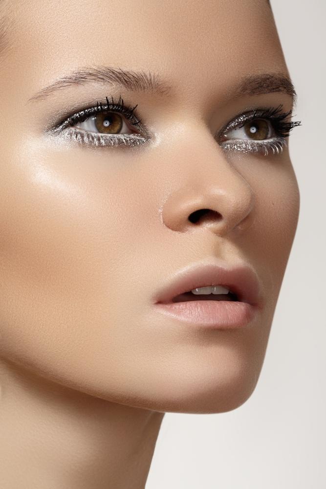 Die Augen einer Frau sind mit einem silbernen Glitter-Make-up umrahmt